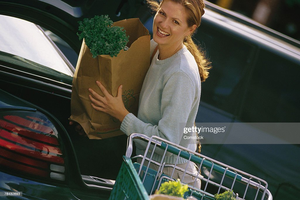 Woman loading groceries into car : Stockfoto