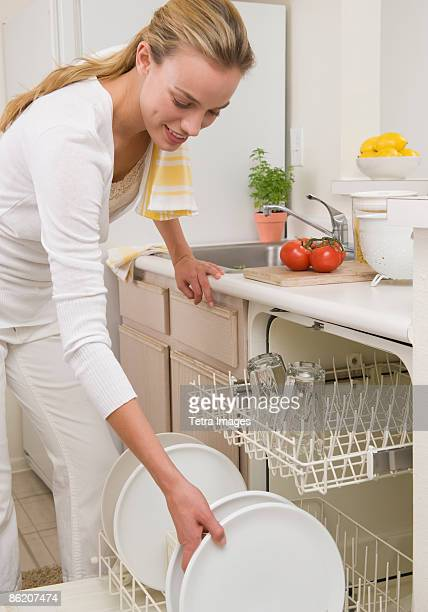 Woman loading plates in dishwasher