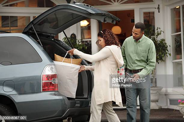 Woman loading shopping bags in boot of car