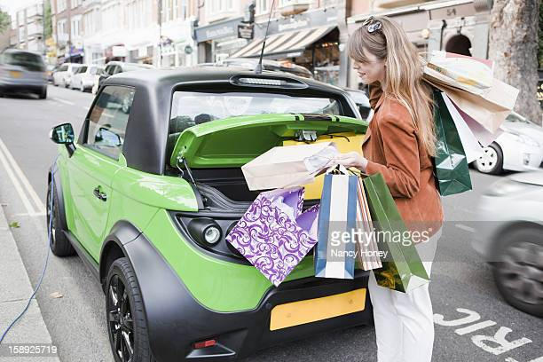 Woman loading shopping bags in car
