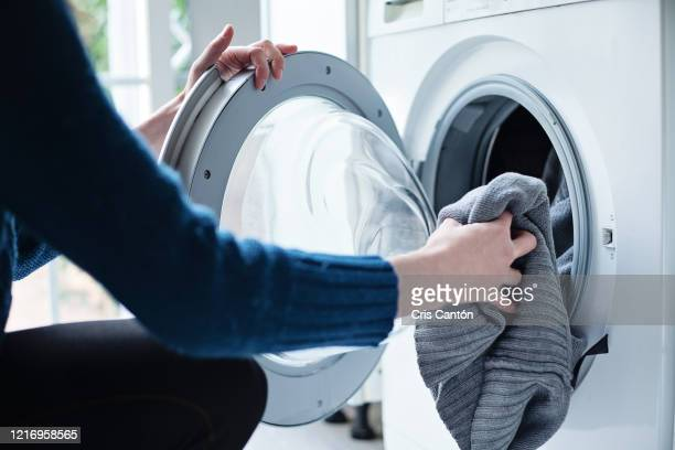 woman loading washing machine - laundry stock pictures, royalty-free photos & images