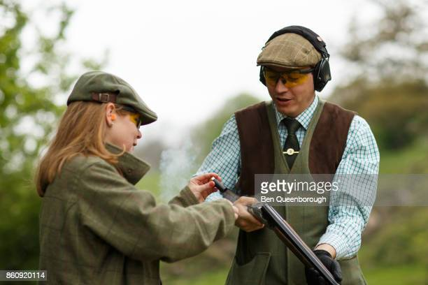 A woman loads her partners rifle during at clay pigeon shoot
