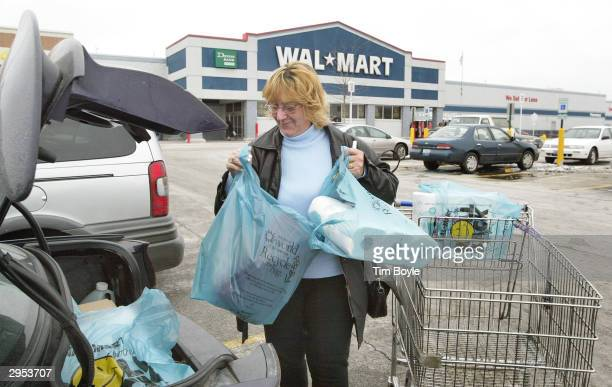 A woman loads her purchases into her car's trunk outside a WalMart store February 9 2004 in Niles Illinois WalMart may be entering a deal with Time...