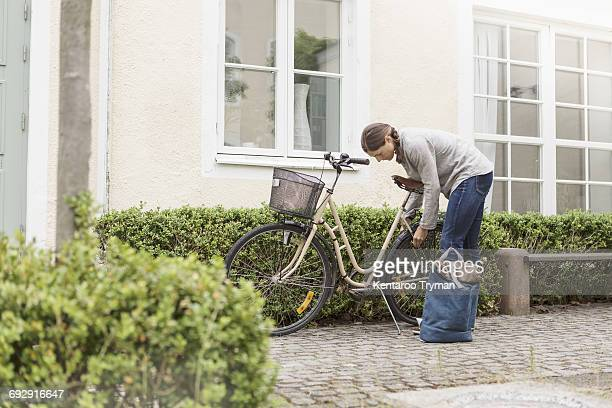 Woman locking bicycle by plants outside house