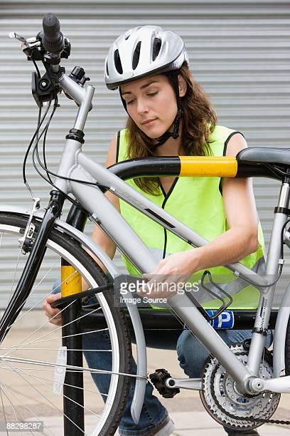 Woman locking bicycle