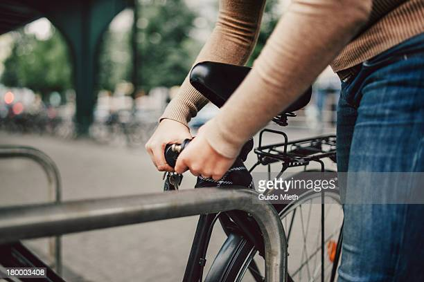 Woman locking her bicycle in city.