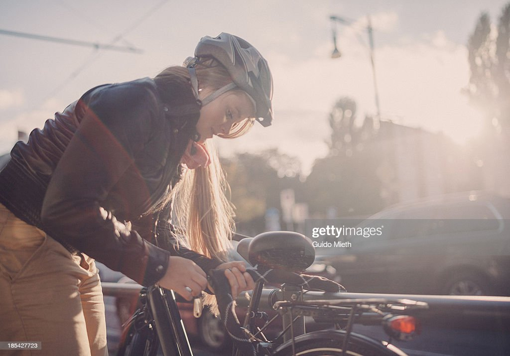 Woman locking her bike in city. : Stock Photo