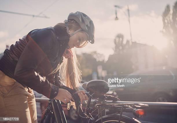 Woman locking her bike in city.