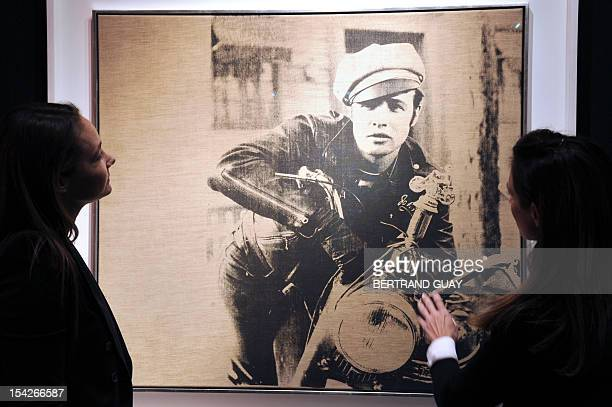 A woman look at a painting 'Marlon' 1966 by artist Andy Warhol and presented by US auction house Christie's as part of the sale 'Postwar and...