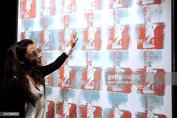 A woman look at a painting 'Statue of Liberty' by artist Andy Warhol and presented by US auction house Christie's as part of the sale 'Postwar and...