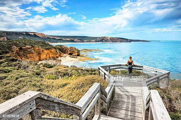 a woman look at ocean at bells beach near torquay, victoria, australia, south pacific - victoria australia stock pictures, royalty-free photos & images