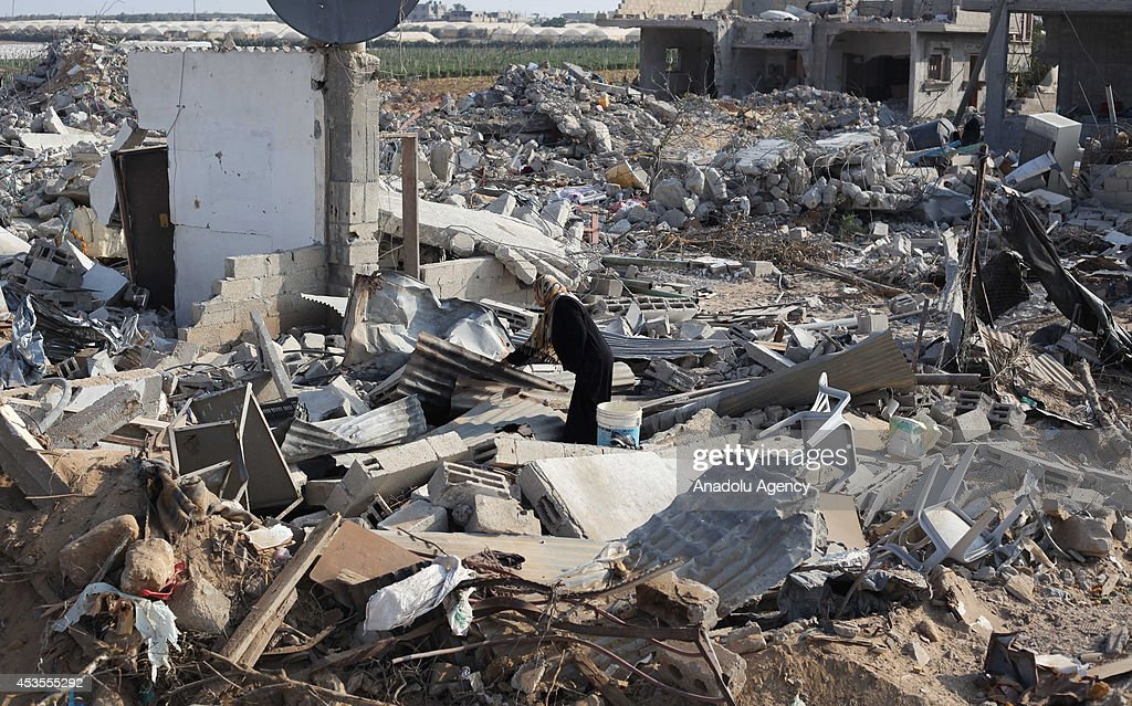 A woman look for usable belongings among the ruins of Fehari area of Khan Yunis as Palestinians try to survive in poor conditions in rambling tents after Israeli strikes in Khan Yunis, Gaza on August 13, 2014.