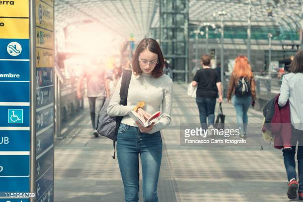woman looking a map in a train station - information symbol stock pictures, royalty-free photos & images