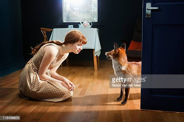 woman looking and talking to fox in livingroom. - fairytale stock pictures, royalty-free photos & images