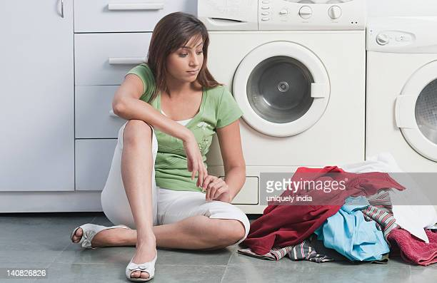 woman looking at a heap of clothes - female mound stock pictures, royalty-free photos & images