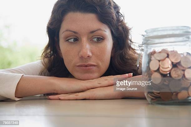 woman looking at a jar of pennies - a sense of home stock photos and pictures