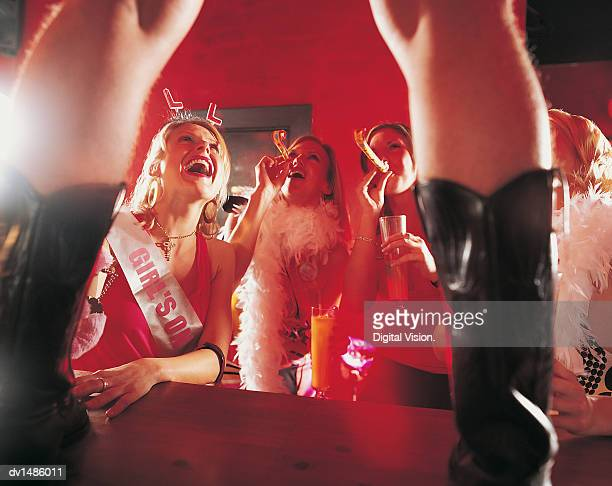 woman looking at a male stripper standing on a bar counter at a hen night - chippendales photos et images de collection