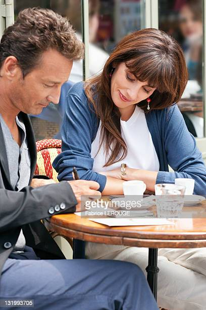 Woman looking at a man signing bill in a restaurant, Paris, Ile-de-France, France