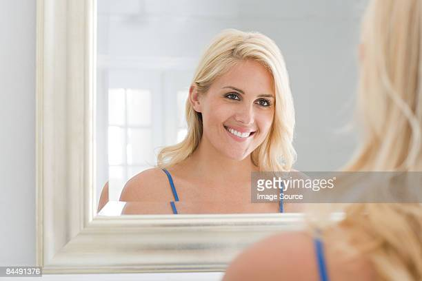 a woman looking at a mirror - woman in mirror stock photos and pictures