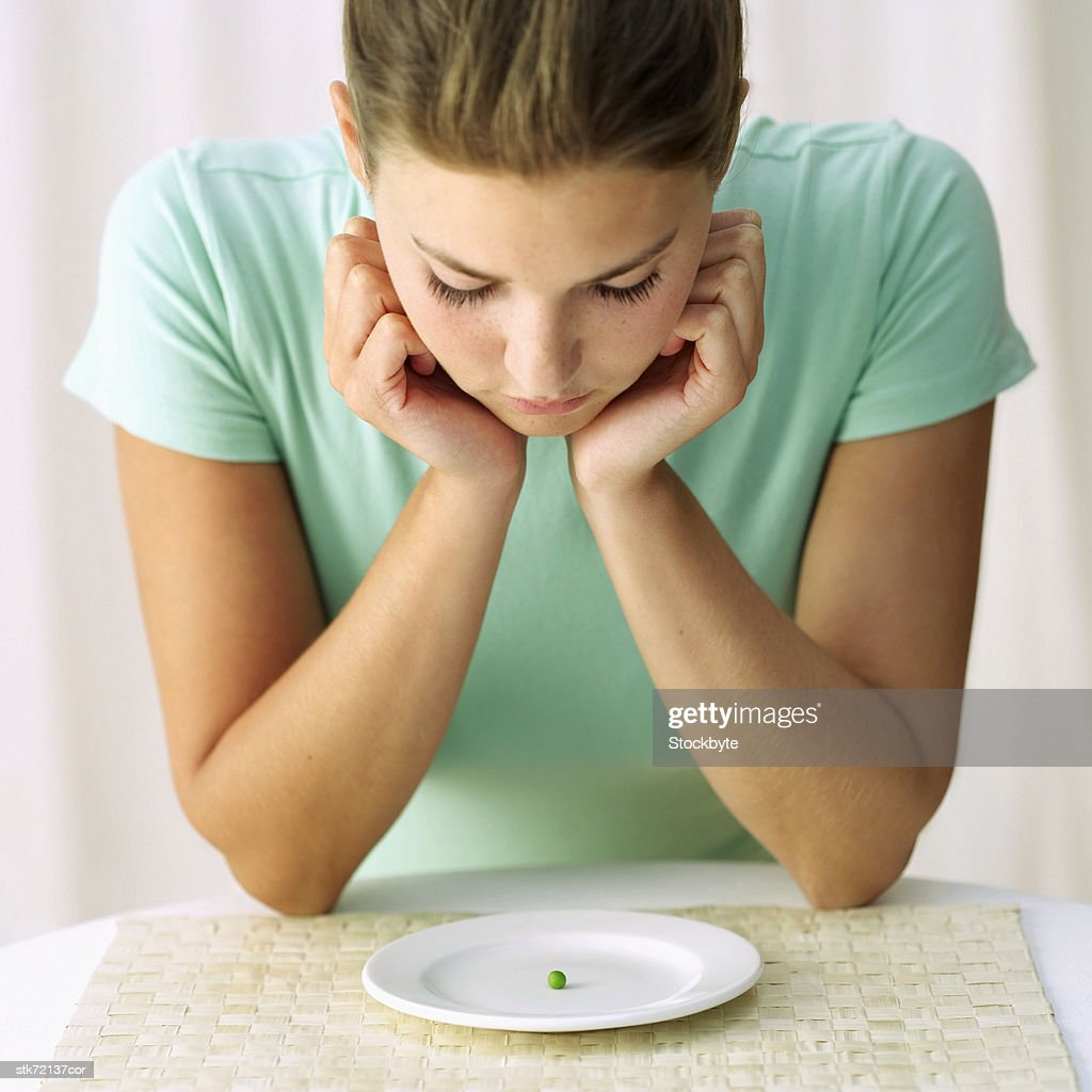 woman looking at a pea on a plate : Stock Photo