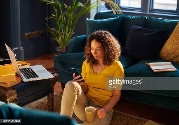 woman looking at a phone - living room stock pictures, royalty-free photos & images