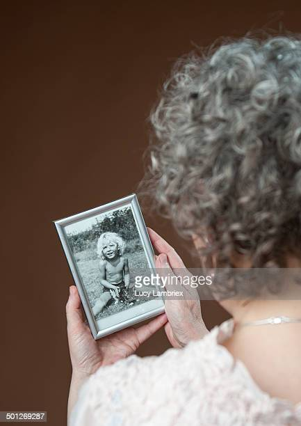 woman looking at a photo of herself as a child - white hair stock pictures, royalty-free photos & images