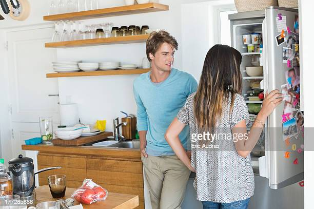 Woman looking at a refrigerator with her husband in the kitchen