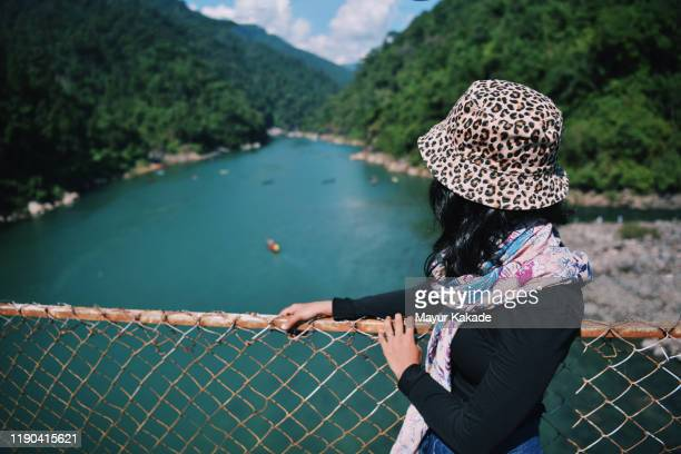 woman looking at a river view from the bridge - チューリップ帽 ストックフォトと画像