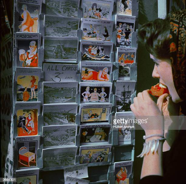 Woman looking at a selection of seaside postcards.