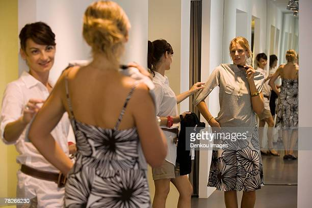 a woman looking at a shirt in a store. - fitting room stock pictures, royalty-free photos & images