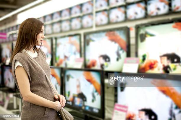 a woman looking at a wall of televisions for purchase - electronics store stockfoto's en -beelden