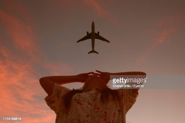 woman looking at airplane against sky during sunset - airplane sky stock pictures, royalty-free photos & images