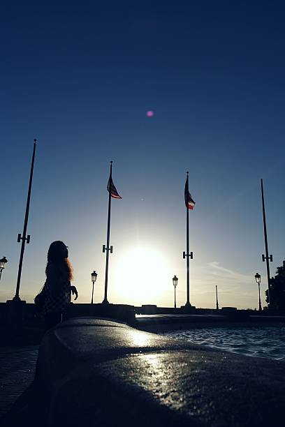 Woman Looking At American Flags By Lake Against Sky