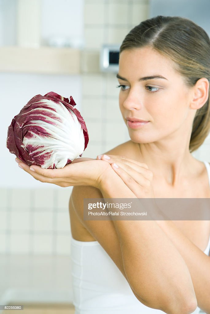 Woman looking at and holding a head of radicchio lettuce : Stock Photo