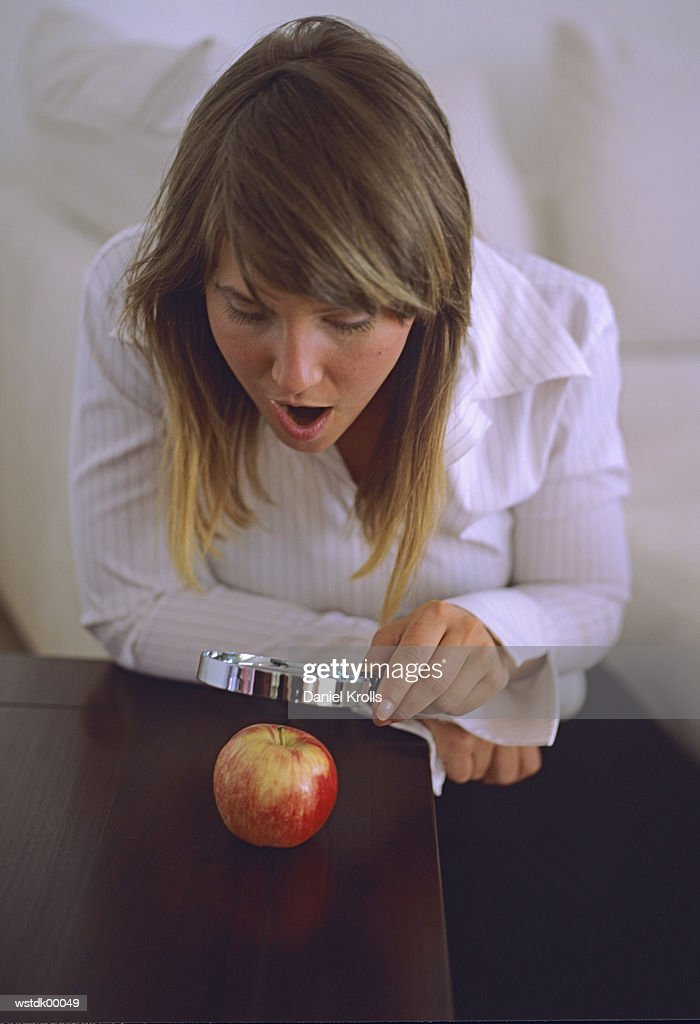 Woman looking at apple through magnifying glass : Stock Photo