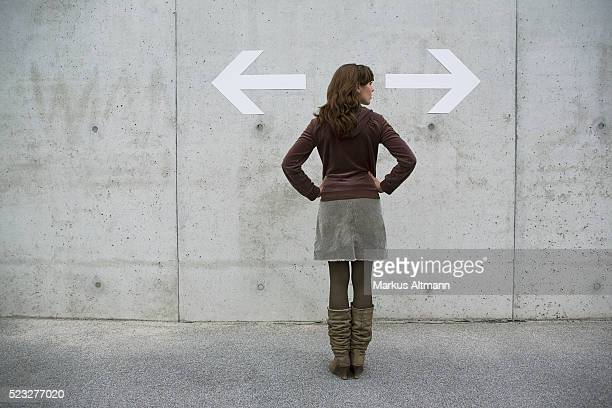 Woman looking at arrows on a wall