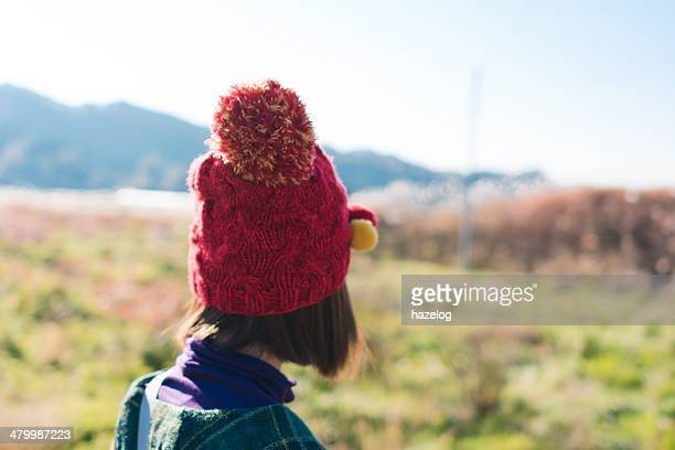 Woman looking at autumn field in the soft sunlight