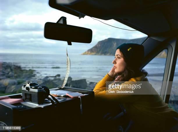 Woman looking at  beach on Lofoten islands from camper van