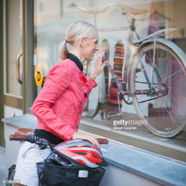 Woman looking at bicycle in window display