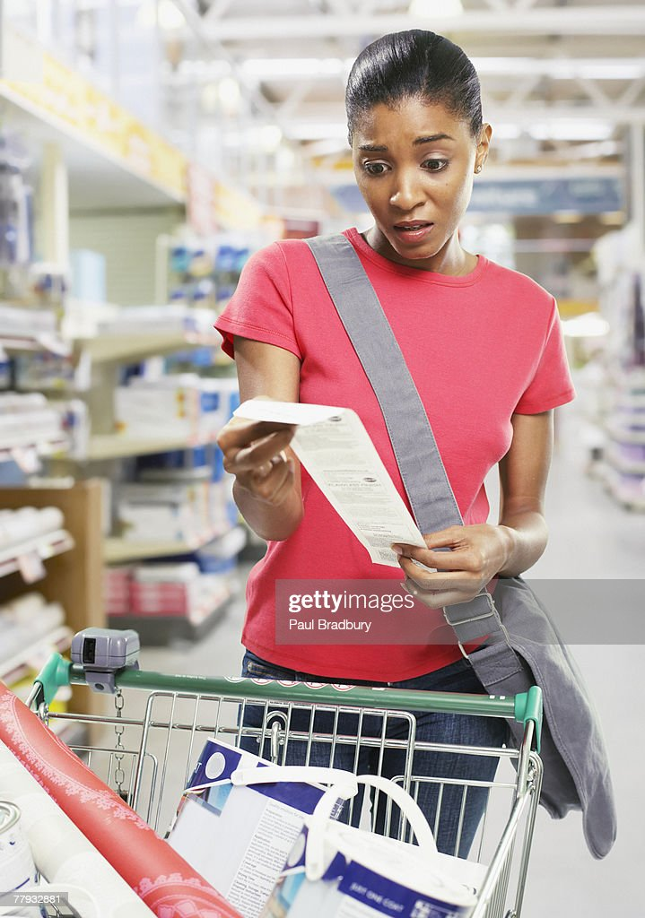 Woman looking at bill in store : Stock Photo