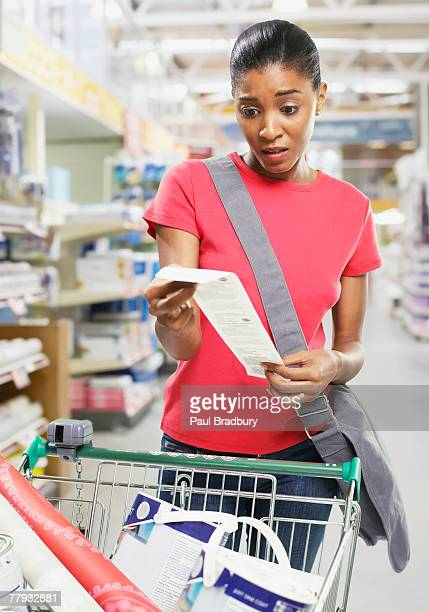 Woman looking at bill in store