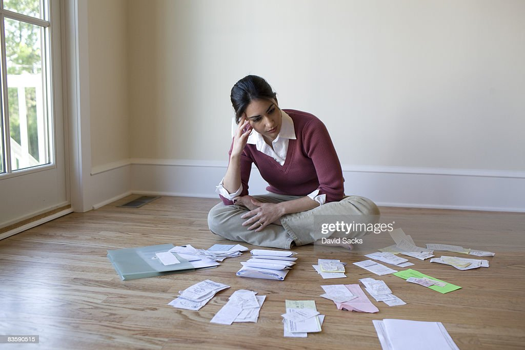Woman looking at bills and receipts on floor : Stock Photo