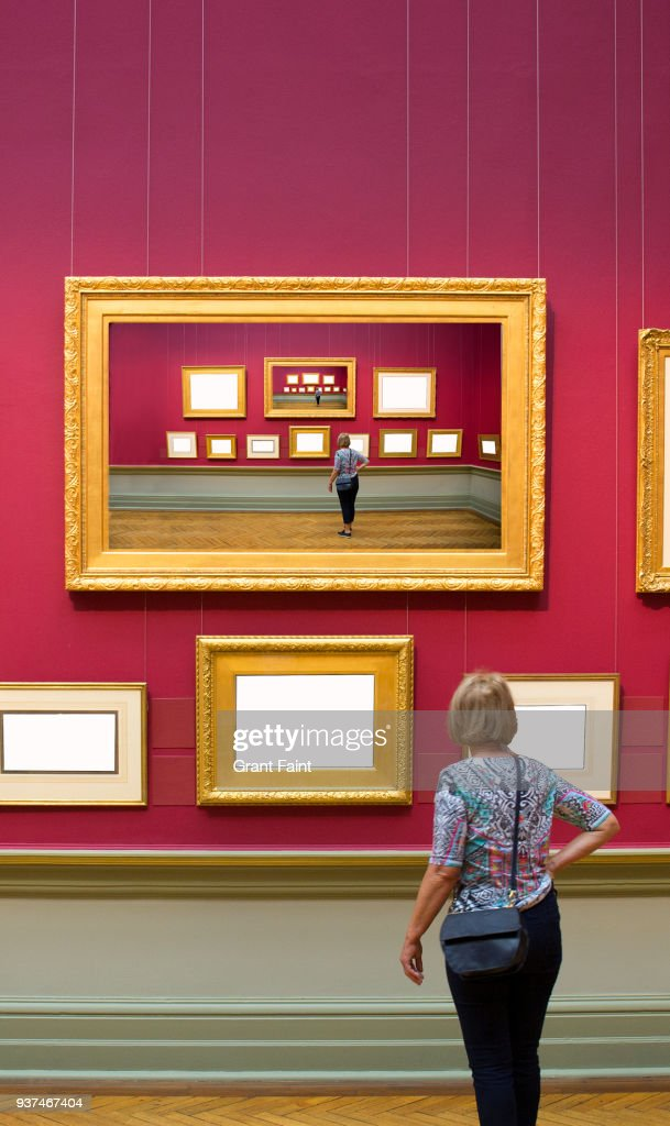 Woman Looking At Blank Frames Hanging On Wall Stock Photo | Getty Images