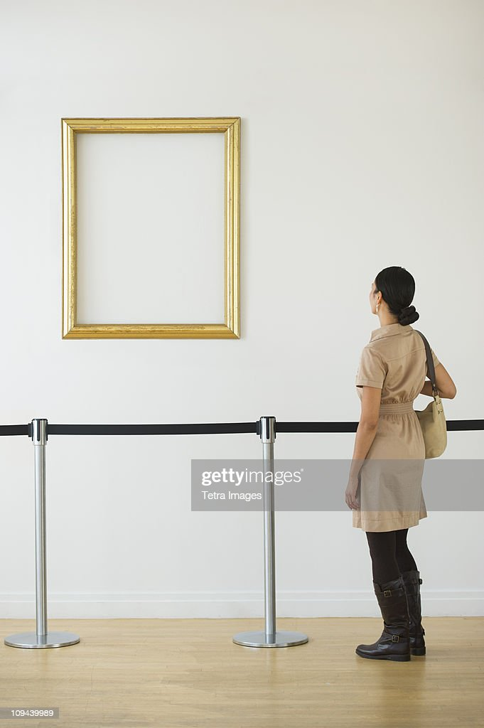 Woman looking at blank picture frame in art gallery : ストックフォト