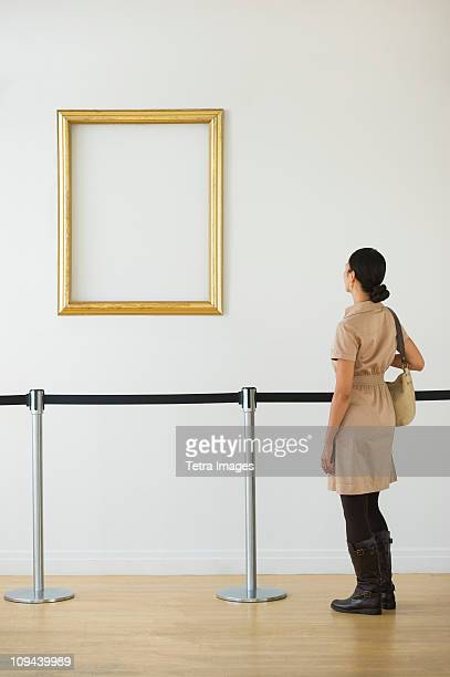 woman looking at blank picture frame in art gallery - museo fotografías e imágenes de stock