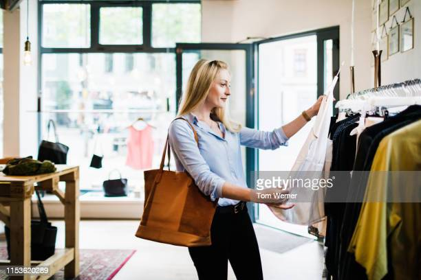 woman looking at blouse while shopping for the day - blue purse stock pictures, royalty-free photos & images