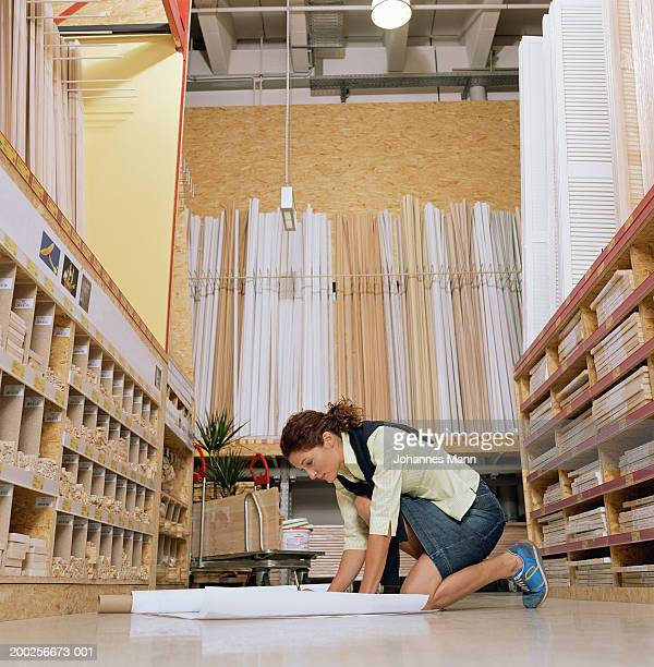 Woman looking at blue prints on floor of hardware shop