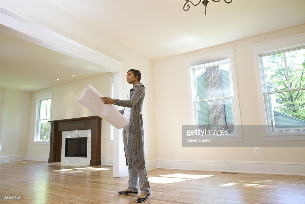 Woman looking at blueprints in newly built home : Stock Photo