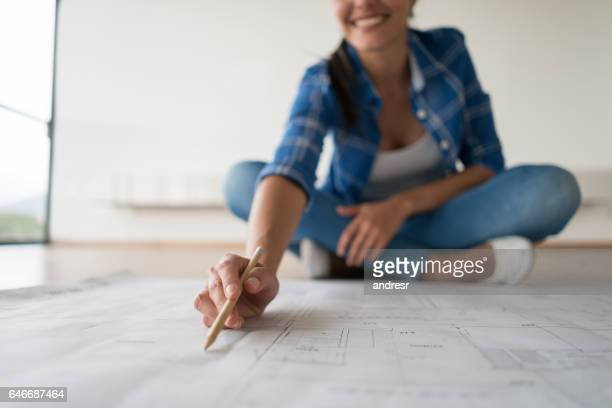 Woman looking at blueprints of her house
