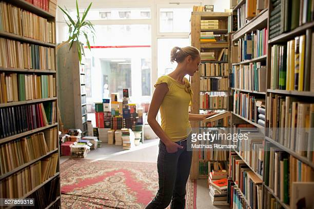 woman looking at books in bookstore - 書店 ストックフォトと画像